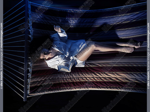 Dramatic portrait of a young woman reading a book in a hammock in a cottage home at night in dim light