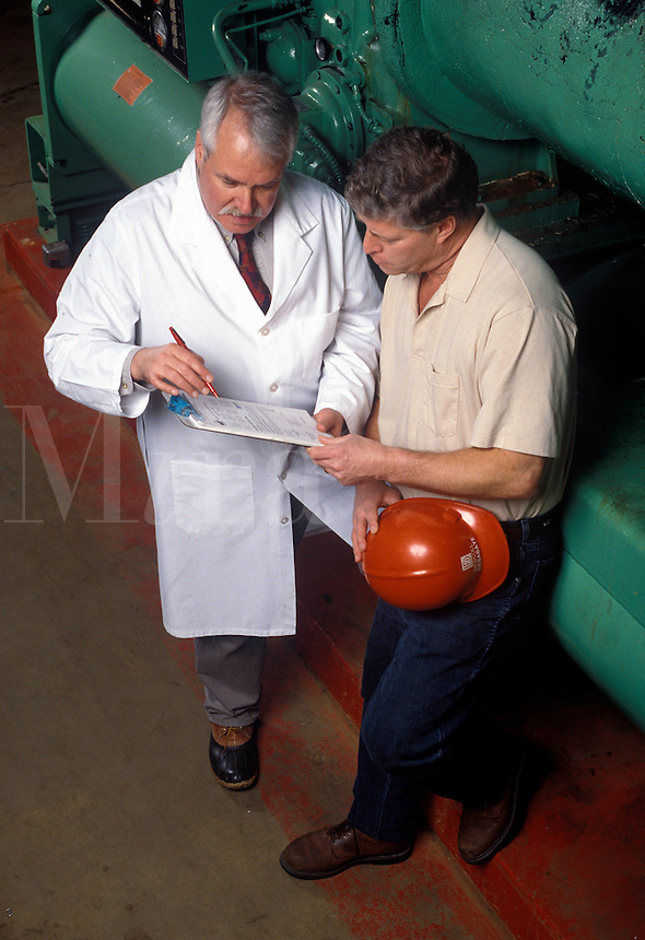 Occupational health professional discusses risk assesssment with factory manager.