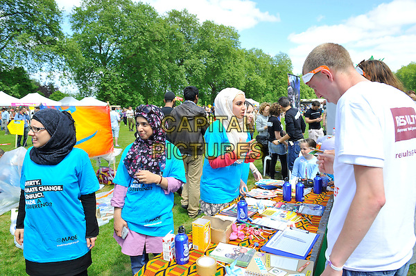 market stalls<br /> attending The Big IF, Hyde Park, London, England. <br /> 8th June 2013<br /> half length gv general view concert goers hajib blue turquoise t-shirt table<br /> CAP/MAR<br /> &copy; Martin Harris/Capital Pictures