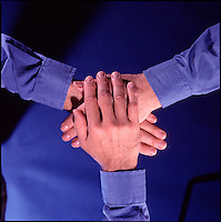 Three hands stacked on top of each other, viewed from above