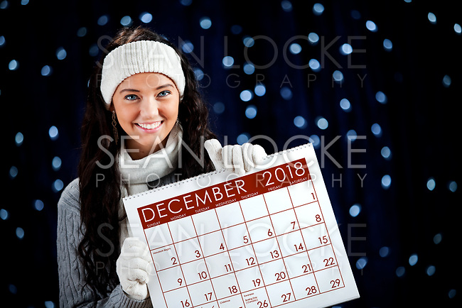 Pretty Caucasian girl in winter clothing on a blue background with glowing white lights.