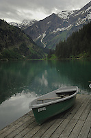 Rain drops falling and rowing boat on wooden jetty. Lake Visalpsee, Reutte district. Austria.