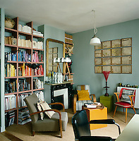 The blue sitting room has a retro feel with a variety of seating styles. Books and magazines are neatly arranged on open shelving set in the recesses either side of the simple fireplace