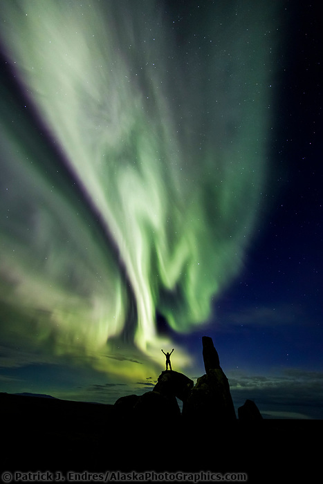 Man stands on a granite tor while the aurora swirls overhead in the Bering Land Bridge National Preserve, Seward Peninsula, Alaska.
