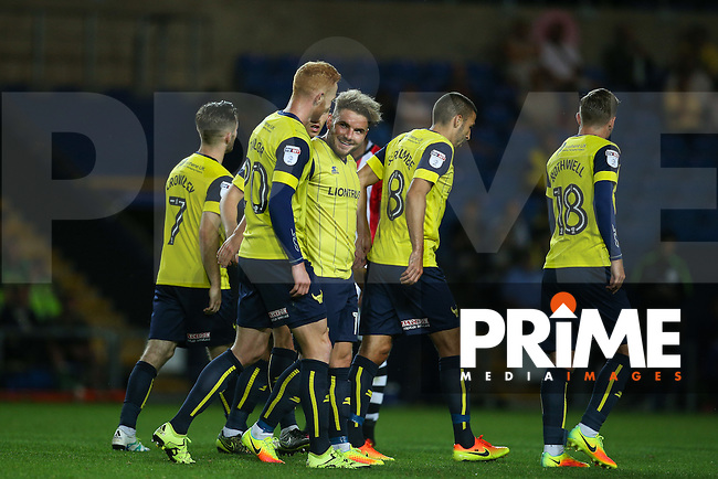 Goalscorer Alex MacDonald (centre) of Oxford United smiles after scoring a stunning goal to make it 4-2 during the The Checkatrade Trophy match between Oxford United and Exeter City at the Kassam Stadium, Oxford, England on 30 August 2016. Photo by Andy Rowland / PRiME Media Images.