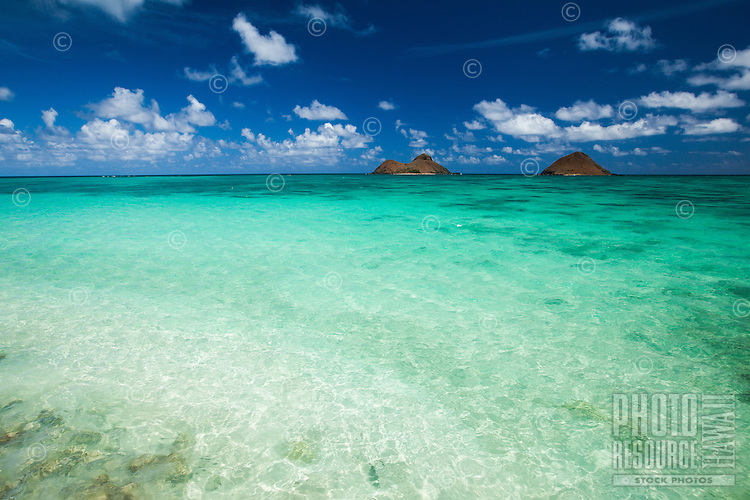 Lanikai Beach's water is clear enough to see submerged reefs, with bird sanctuaries Moku Nui and Moku Iki Islands (or Mokulua Islands) in the distance, O'ahu.