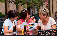 Tourist girl friends relax with drinks and look at postcards and have fun in Old Havana in Habana Cuba