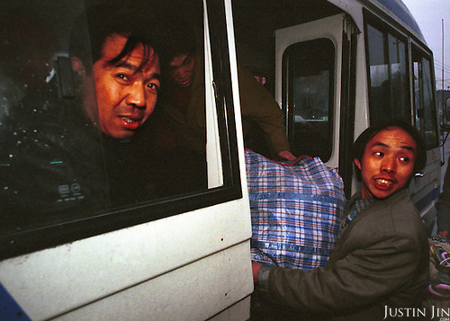 Wei gets on a bus in Beijing at the start of a journey to Sichuan...Wei is taking his wife and two children home to Sichuan after living in the garbage dump for one year. He plans to put his children to school before returning alone to look for work in Beijing. ..Picture taken April 1999.Copyright Justin Jin