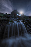 Waterfall illuminated by the night sky. Glacier National Park, MT