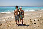Model released smiling brother and sister twins stand on sandy beach together, Rhodes, Greece,