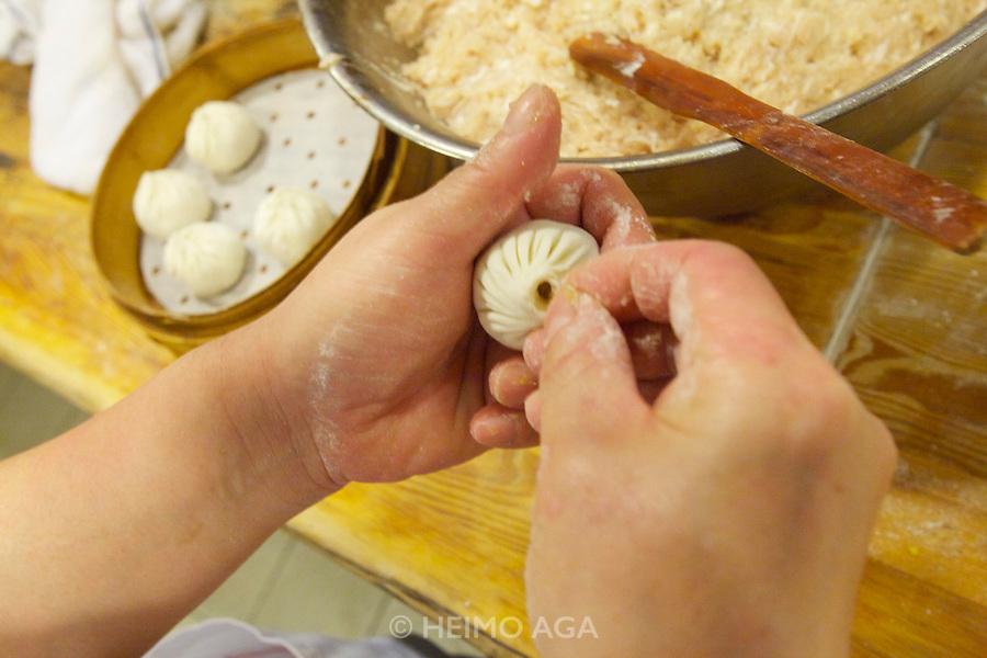China, Hong Kong S.A.R..Nanxiang Steamed Bun - Causeway Bay. The chefs at the kitchen..Making of Nanxiang Steamed Buns.