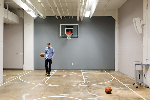 February 18, 2015. Winston Salem, North Carolina.<br />  Nick Sebesta, an employee of the branding company Astronaut, shoots hoops on the basketball court of Flywheel, a co-working space, which is  part of the 525 @ vine building on the Wake Forest Innovation Quarter's campus.<br />  The Wake Forest Innovation Quarter, encompassing 145 developable The Wake Forest Innovation Quarter, encompassing 145 developable acres, is an inner city development project focusing on biomedical sciences and information technology. The project is a collaboration between the city of Winston Salem, a private developer and Wake Forest University.The newest building in the $500 million project is a $50 million education building for the university's medical school. Many professional firms have moved into offices in the various buildings of the Innovation Quarter as the city shifts from a tobacco town to one of technological advancement.