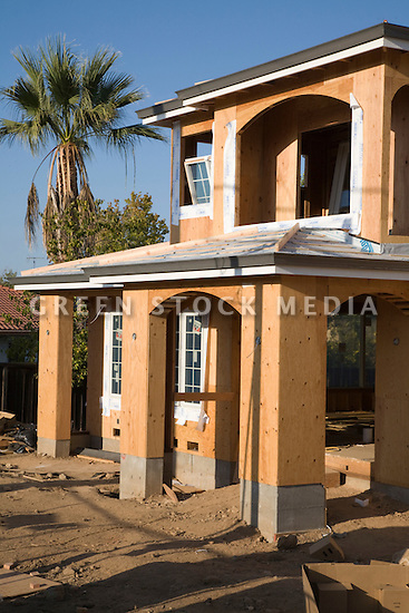 A California Palm rises into a blue sky next to a two-story wood frame house under construction in Cupertino, California, in Silicon Valley of the San Francisco Bay Area.