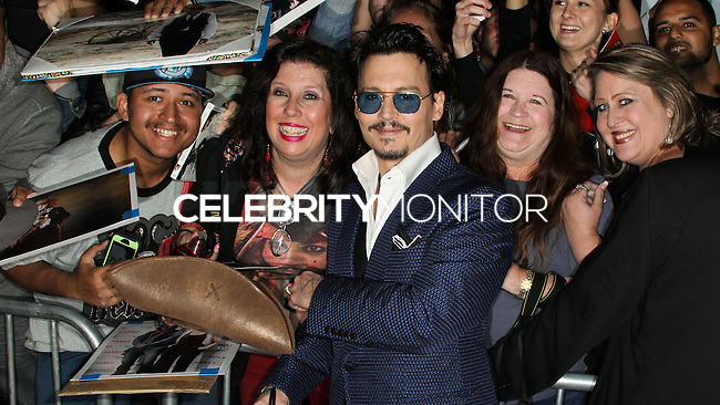 "WESTWOOD, LOS ANGELES, CA, USA - APRIL 10: Actor Johnny Depp signs autographs for fans as he arrives at the Los Angeles Premiere Of Warner Bros. Pictures And Alcon Entertainment's ""Transcendence"" held at Regency Village Theatre on April 10, 2014 in Westwood, Los Angeles, California, United States. (Photo by Xavier Collin/Celebrity Monitor)"
