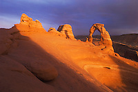 Delicate Arch at sunset with lightning strikes, Arches National Park, Utah, USA