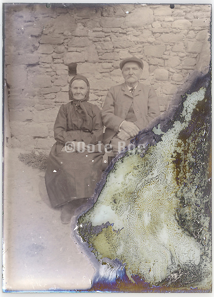 portrait of sitting senior couple on a severely eroding glass plate