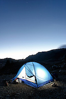 Backpacking tent glowing below night sky, near Yellow Aster Butte, North Cascades, Whatcom County, Washington, US
