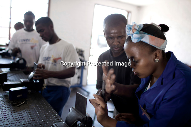CAPE TOWN, SOUTH AFRICA - APRIL 20: Layanda Mduka (r) , age 20, works in the shop on April 20, 2012 in Cape Town, South Africa. She studies at a motor mechanics course who is dedicated to training five apprentices at a time, in motor car mechanics. The students come from poor backgrounds and have been unemployed until they cam here. iThemba Labantu offers these young men and women the opportunity to learn a trade so that they will be able to earn a living for themselves and their families one day. (Photo by Per-Anders Pettersson For Global Post)