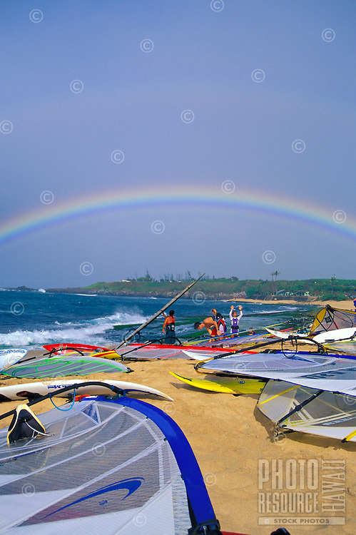 Windsurfers relax on Hookipa Beach Park with a rainbow overhead. Just outside the town of Paia along the Hana Highway is Maui's best and most popular beach park for surfing and windsurfing. Hookipa means hospitality in Hawaiian.
