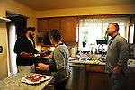 Mike Padgett, 30, his aunt, Marianne Padgett, and cousin Garrick Leitelt, 38, making bacon pizza for dinner at home in Chicago Ridge, Illinois on April 21, 2015.  All three live under the same roof along with Mike's dad Wayne; Padgett is a student at the University of Illinois Chicago doing an externship in the neuroscience imaging and microscopy lab and bar tends at the Drum and Monkey on campus for extra cash.