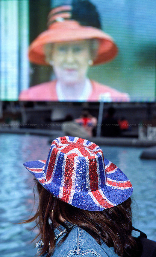 A tourist,wearing a Union Jack hat watches a large TV screen in Trafalgar Square showing an image of Queen Elizabeth the Second of Britain, during the Golden Jubilee celebration in London. England, United Kingdom Tuesday June 4th  2002