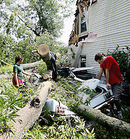 Diana Birney, left, and her borther Justin Birney look at their crushed 1966 Ford Mustang in the driveway of their Anderson home Wednesday. A tree that fell during Tuesday's storm damaged the house before landing on the car.