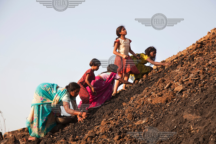 Women from the village of Kujama collect coal from the overburden dump for a nearby open pit coal mine. Overburden is the fertile soil (formerly used for agriculture) that has to be removed to get at the coal underneath. In the process small pieces of coal are also picked up which are scavenged by local villagers and sold for cash.