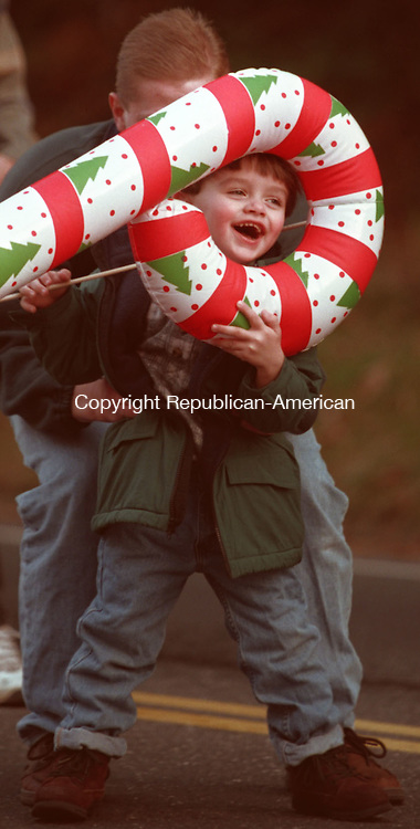 SEYMOUR, CT 11/29/98 --1129JH01.tif--Steve Machnicz, Jr., 3, of Ansonia laughs as he peeks through his inflatable candy cane at the annual Christmas parade in Seymour Sunday. That's his father Steve behind him. JOHN HARVEY staff photo for Thomas story.