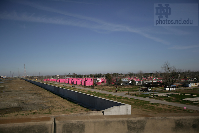 "Lower Ninth Ward, New Orleans. Repaired Industrial Canal floodwall and levee are on the left, ""Pink Project"" houses are visible in the Lower Ninth Ward on the right.  The Pink Project is a grouping of fabric-covered scaffolding in the shape of houses on former Ninth Ward home sites--a ""Virtual City of Hope"" to raise awareness and money.  The project was spearheaded by actor Brad Pitt."