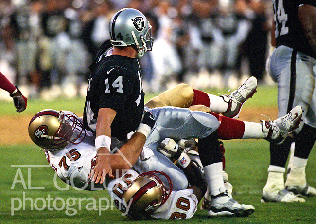 Oakland Raiders vs. San Francisco 49ers at Oakland Alameda County Coliseum Monday, August 30, 1999.  49ers beat Raiders  16-8 in a preseason game.  Oakland Raiders quarterback Bobby Hoying (14) is sacked by San Francisco 49ers defensive tackle Matt Keneley (75).