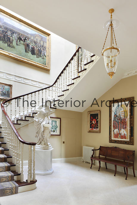 An array of paintings from different eras and styles adorn the walls of the entrance hall and staircase