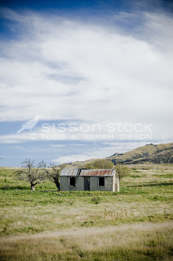 Historic cob cottage in field near central otago rail trail at Hyde New Zealand. Blue sky with white clouds.