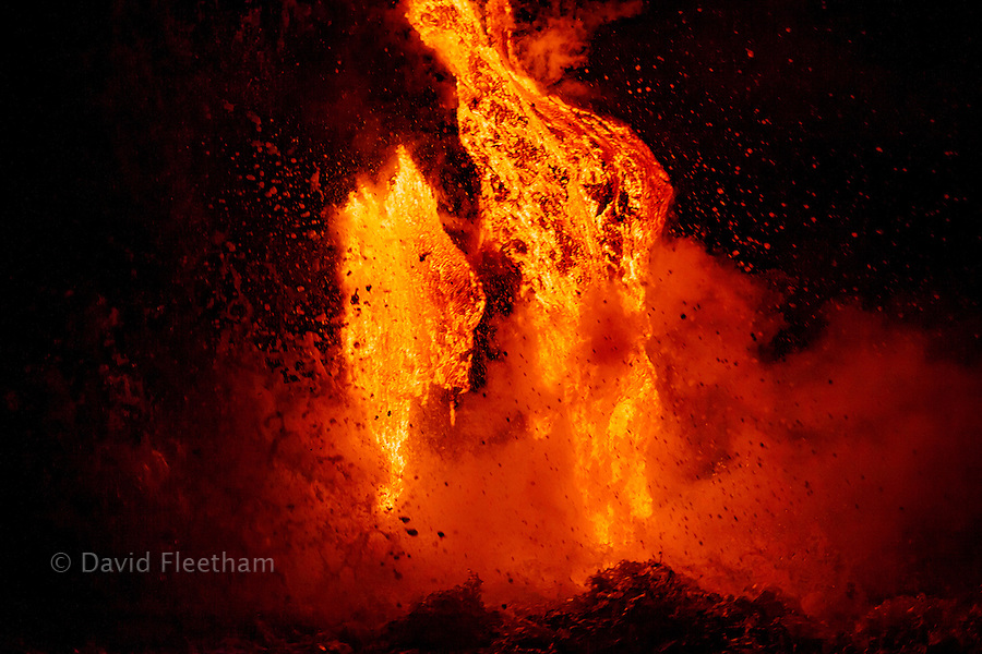 Sea water and molten rock splatter just before sunrise as Pahoehoe lava flowing from Kilauea reaches the Pacific ocean near Kalapana, Big Island, Hawaii.