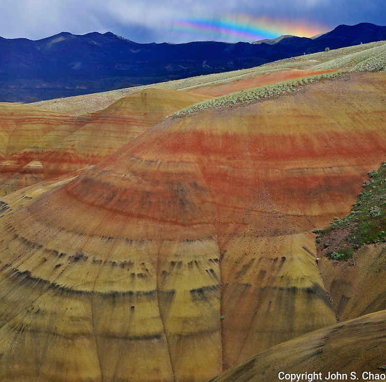Section of Painted Hills with a distant rainbow above. John Day Fossil Beds National Monument. Mitchell, Oregon.