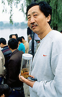China. Province of Beijing. Beijing. Xihai lake. A chinese man dressed with a gray Nike sweat-shirt holds in his hand a bottle of tea and his mobile phone.  © 2004 Didier Ruef