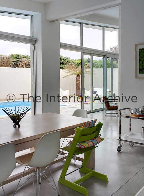 A child's high-chair painted a vibrant green with a cheerful striped cushion faces out towards the enclosed terrace where there is an outdoor swimming pool