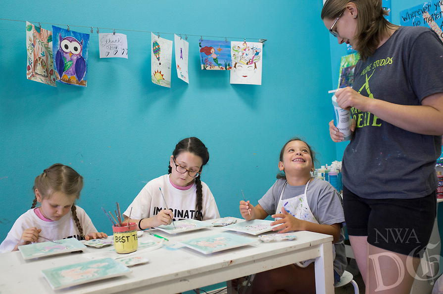 NWA Democrat-Gazette/CHARLIE KAIJO Instructor Hannah Gottschalk (right) helps Emery Kloster of Bentonville, Ella Kloster of Bentonville and Katie Segura of Rogers (from left) during an art camp, Monday, August 5, 2019 at Imagine Studios in Rogers.<br /> <br /> Imagine Studios owner Melanie Hewins held an art camp called Unicorn Dreams. Kids decorated unicorn themed plates and unicorn and rainbow magnets. The camp runs till Thursday. Kids learn how to use acrylic paints and water colors and canvas and ceramic painting.