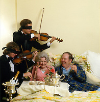 Mature couple with blindfolded musicians demonstrate part of an expensive weekend of food and entertainment.