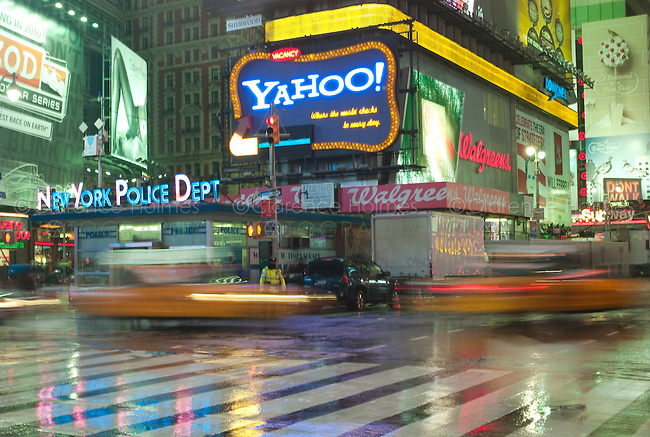 Motion blurred abstraction of taxis rushing through Times Square on a rainy evening