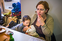 A mother breastfeeding her baby in a museum cafe while her older son talks to the baby.<br /> <br /> London, England, UK<br /> 08/03/2015<br /> <br /> &copy; Paul Carter / wdiip.co.uk