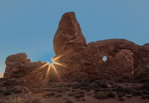The sun sets behind Turret Arch at Arches National Park, Utah