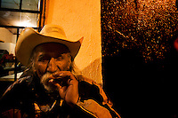 A member of a &quot;Trio band&quot; smoking tobacco cowboy style. <br /> <br /> In northern mexico bands known as &quot;trios&quot; are well known for their services, private playings. In restaurants, bars or in the street is often see them offering songs, from traditional mexican music like mariachis, banda, corridos to classic rock.
