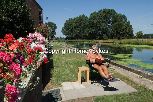 East London the site of the 2012 Olympic Games Park,  Hackney Marsh, Stratford, England 2006.Peter Rollinson 25 years resident on Kingsmead Estate, reads a book in his lunch hour by his home overlooking the river Lea Navigation canal and Hackney Marsh.