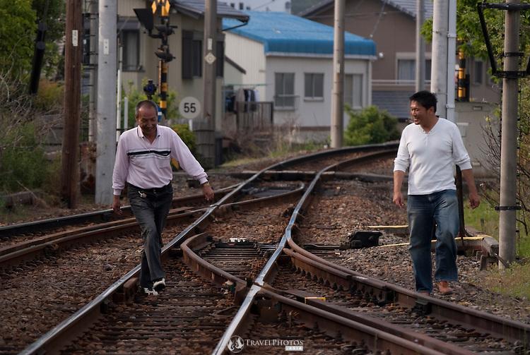 Two men walking along railway tracks of the Yoro Line near Tado Station, Japan.
