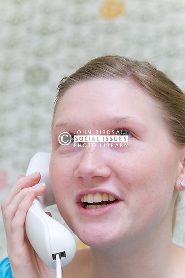 Teenaged girl on work experience placement from school making a telephone call in the work place,