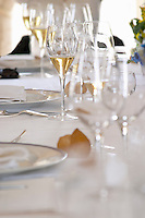 A lunch table with many glasses set up for a wine tasting white plates, silver ware, a white table cloth and bread, Champagne Jacquesson in Dizy, Vallee de la Marne, Champagne, Marne, Ardennes, France