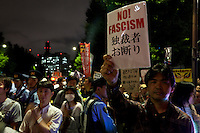"A Japanese man holds a ""No Fascism!"" sign at a protest against the revision of article 9 of the Japanese Constitution outside the Prime-Minister's house in Kasumigasaki, Tokyo, Japan. Monday June 30th 2014. Over 10,000 people showed their support for Japan's unique peace constitution and called on the government to halt its reinterpretation of Article 9 allowing Collect Self Defence which is expected to become law on July 1st"