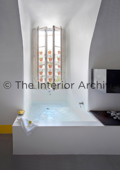"""A contemporary bath has been fitted into the window alcove in the bedroom giving a whole new meaning to """"ensuite"""""""
