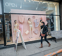Passer-by observe mannequins in the window of an American Apparel store in the Lower East Side neighborhood of New York sport pubic hair showing through and around their underwear, seen on Sunday, January 19, 2014. The company is known for their attention grabbing promotions and has used other shocking imagery that borders on being pornographic. This promotion is the store's Valentine's Day window. (© Richard B. Levine)