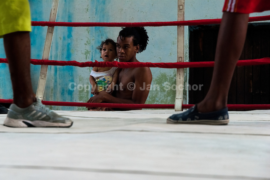 A Cuban baby girl watches young Cuban boxers fighting at Rafael Trejo boxing gym in Havana, Cuba, 13 February 2010. During the last 30 years Cuba has produced more World Champions and Olympic gold medallists in amateur boxing than any other country. Many famous fighters, who came out of Cuba, were training at Rafael Trejo boxing gym in their youth. This run down open air facility in the Old Havana is a place of learning and mastering the art of boxing by the old school style. Boys begin their training very young. As sports are given a high political priority in Cuba, all children are systematically encouraged to develop their skills. Those who succeed will become heroes of Cuban society.
